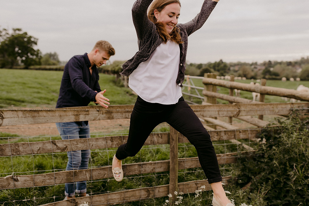girl jumping over fence