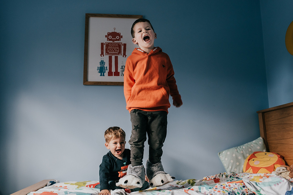 boys jumping on bed