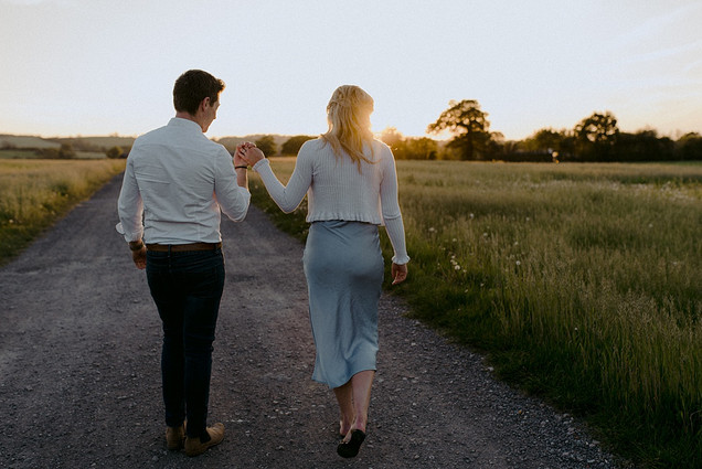 photo of couple in field at golden hour