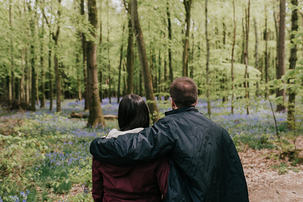 couple walking in wood from back