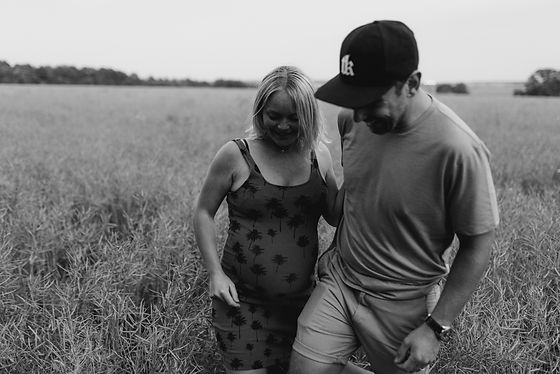couple in field pregnancy photography