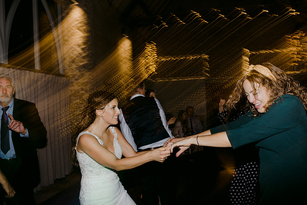 bride dancing with friend on her wedding day