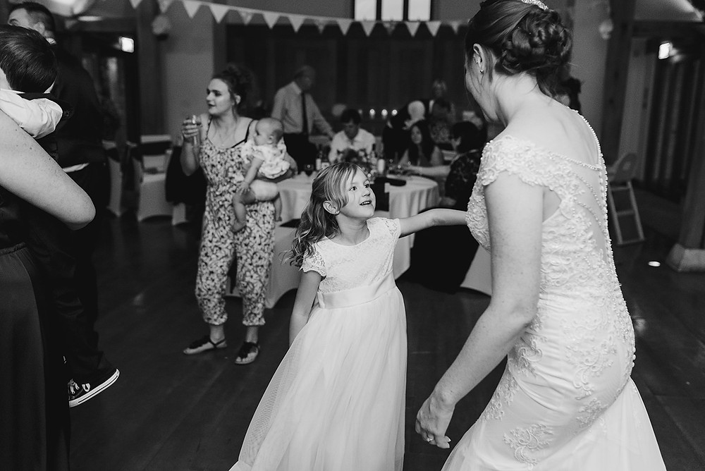bride dancing with flower girl black and white