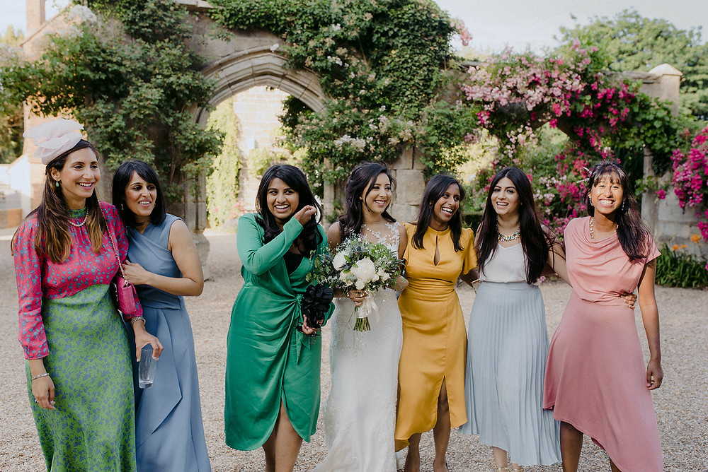bride and bridesmaids in different colourful dresses