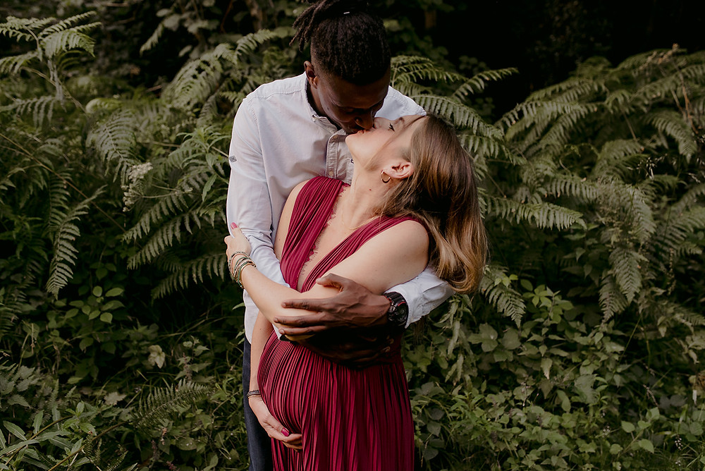 pregnant couple kissing and ferns