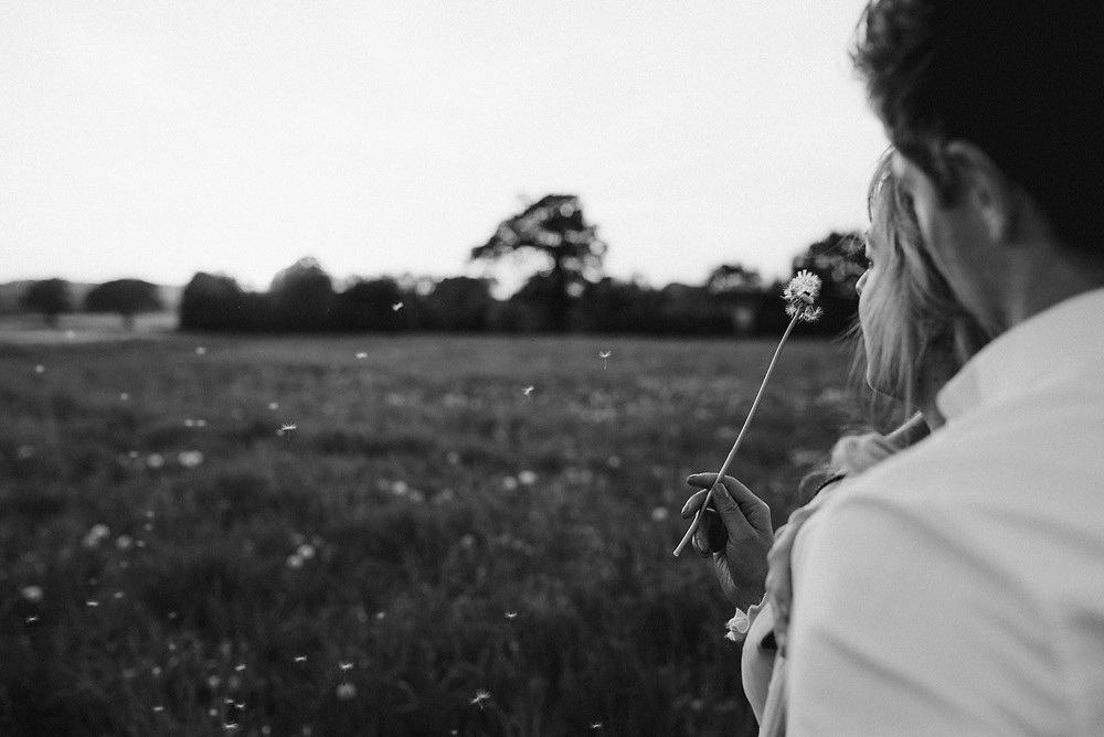 photo of girl blowing a dandelion