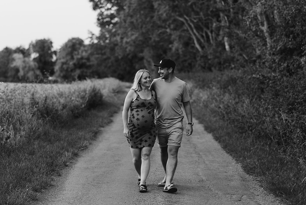 maternity photoshoot couple walking down road