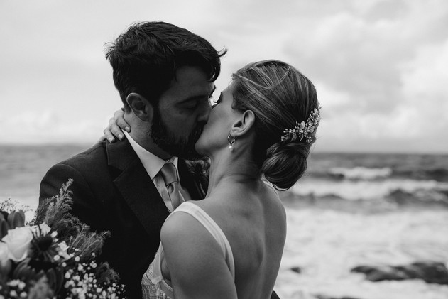 black and white photograph bride and groom kissing