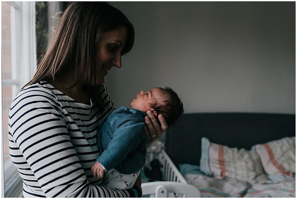 mum and newborn by window