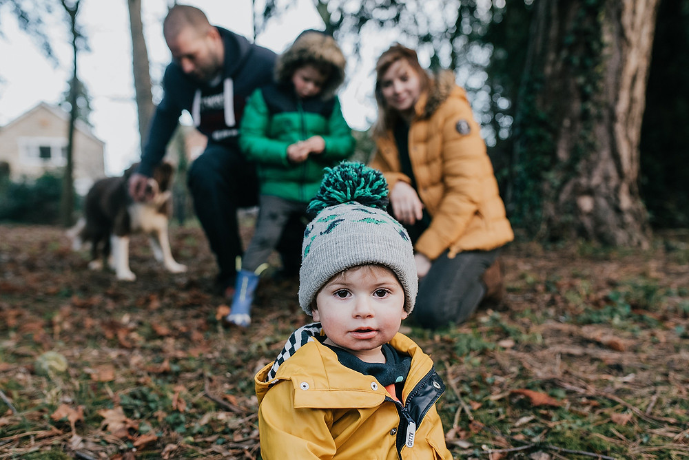 family of four with dog in woods