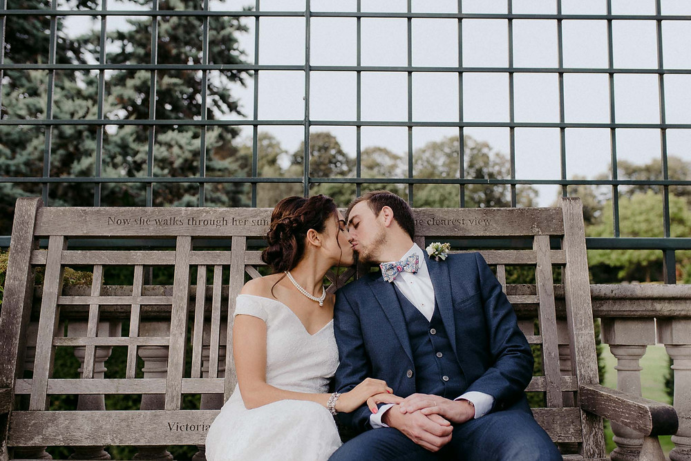 wedding bride and groom kissing on bench