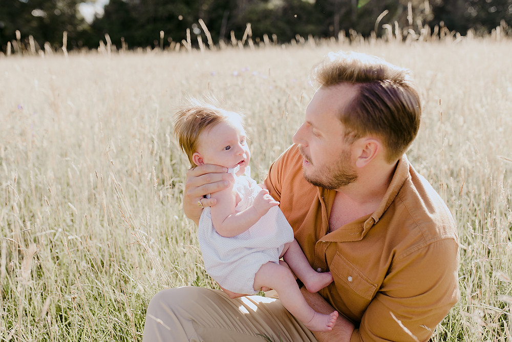 father and newborn daughter in meadow