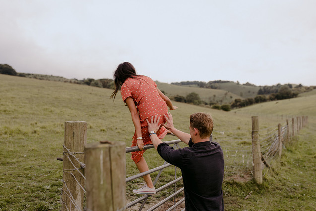 couple climbing over fence in field