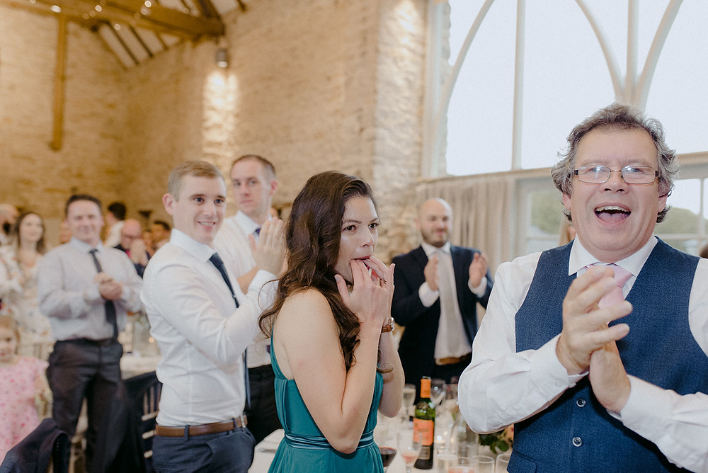 guests cheering at wedding speeches