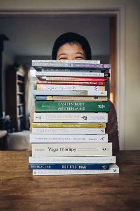 woman sitting behind a pile of yoga books on a desk