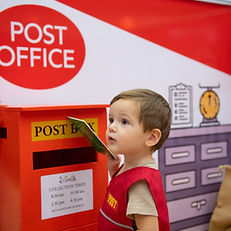 Child posting a letter at the mobile play centre, Little City
