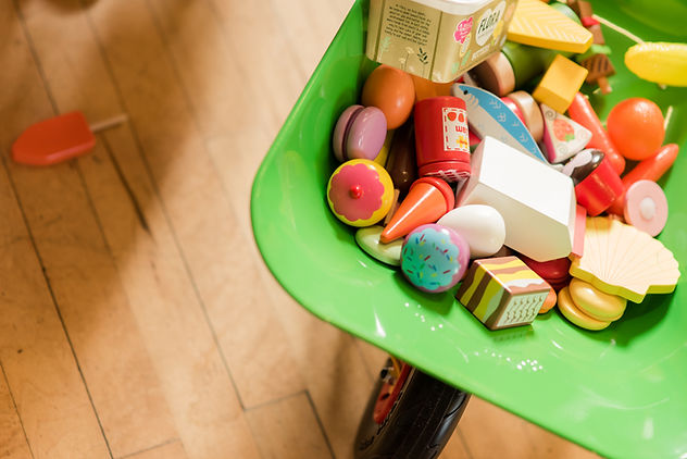 Assortment of wooden toys in a child's wheelbarrow on a wooden floor