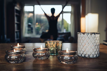 silhouette of a woman doing the yoga tree pose in front of a window and with decorative candles in the foreground