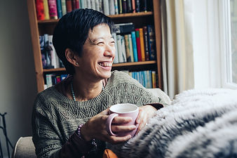 smiling woman with a cup of tea looking out of the window and with a bookshelf in the background