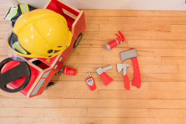 Children's firefighter role play toys on a wooden floor