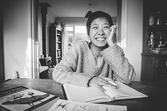 smiling woman sitting at a desk with an open book