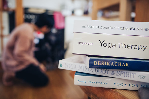 pile of yoga books on a table in the foreground with a woman crouching in the background