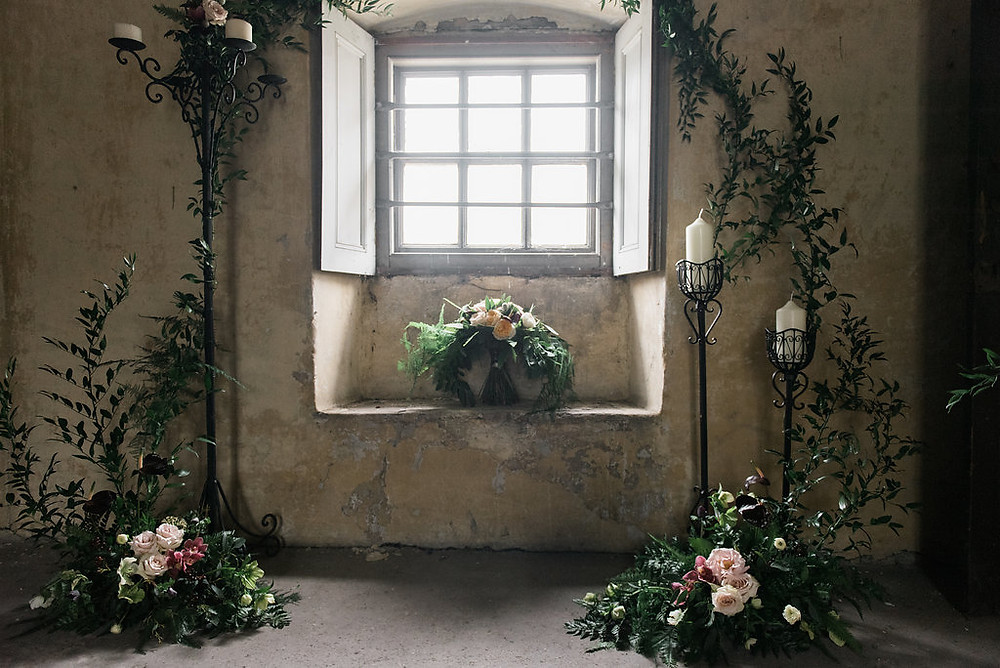 First of all I made arrangements to sit on the floor with black candelabras and placed French ruscus foliage's around to frame and arch effect. There were pins in the wall so I was able to wrap the foliage towards the walls.