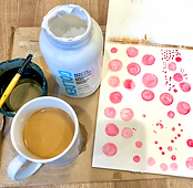 Mug of coffee, Golden's matte medium, page of pink acrylic circles, water cup and fan paint brush.