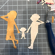 Cut out silhouettes of brown & white men holding hands with their small daughter in-between them.