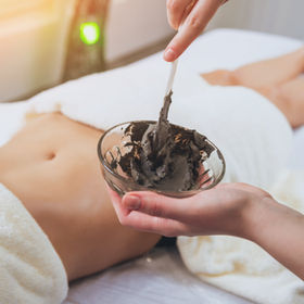 Beautiful woman in spa salon getting mud