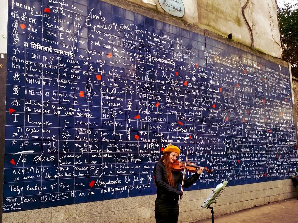 Violoniste demande en mariage paris avec un beret devant le mur des je taimes