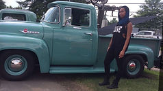 woman standing in front of old school Ford truck at car show