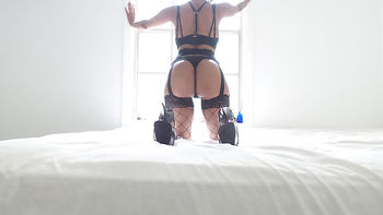 intimate view looking out the window from the bed with heels