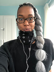 woman with a big twist in her hair a bandana around her neck and glasses on making a silly face