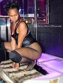woman dressed as a kitty squatting down in front of a stripper pole