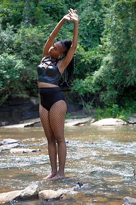 woman standing in a stream stretching her body