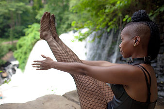 woman near waterful holding navasana boat pose