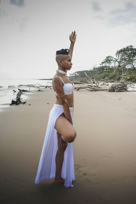 goddess with shaved sides and locs wearing a white flowing skirt in a yoga pose on the beach