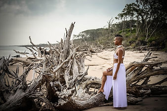 woman with her foot up on a fallen tree on the beach looking out to the ocean