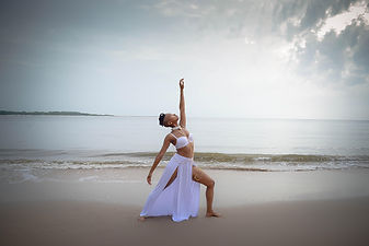 goddess dressed in a flowing white high slit skirt and lace bra doing a yoga pose on the beach with the ocean behind her and the clouds opening up in the sky