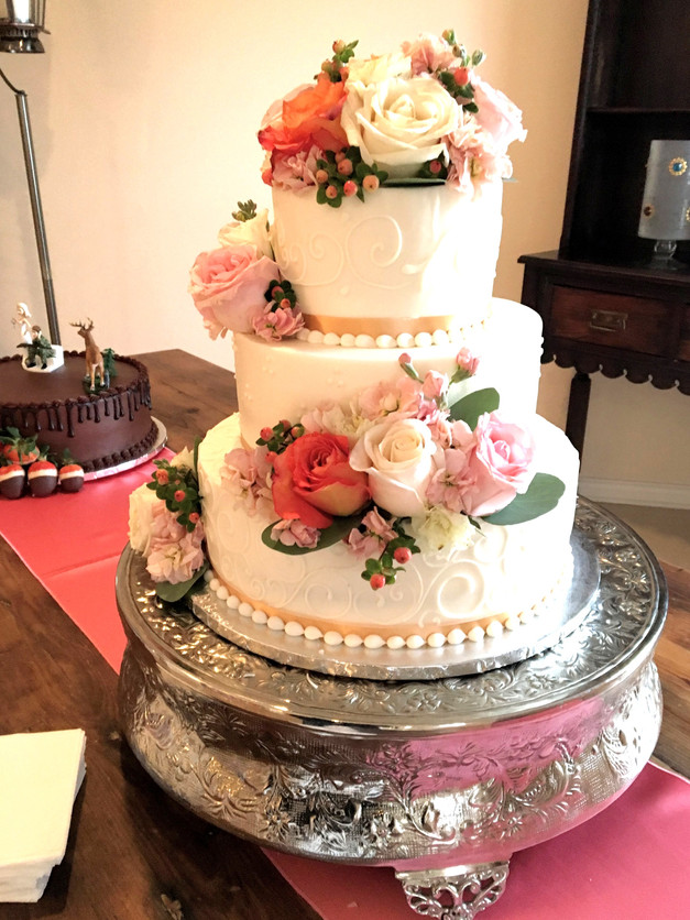 Coral roses make this Candy Haven cake stand out.