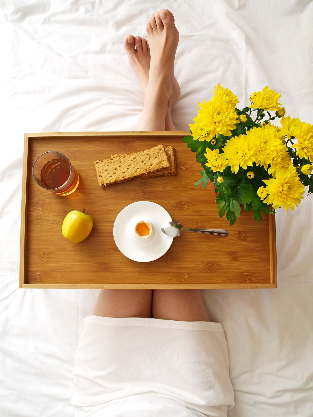 Breakfast tray on the lap of person sitting on bed. It has vase of yellow daisies, dry crackers, boiled egg, apple and cup of tea