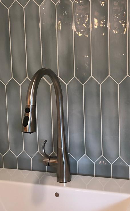 Bathroom tap and sink with tile backsplash