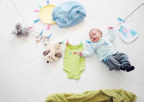 Baby liegt auf dem Boden neben Kleidung, Nachbetreuung in Strasshof an der Nordbahn