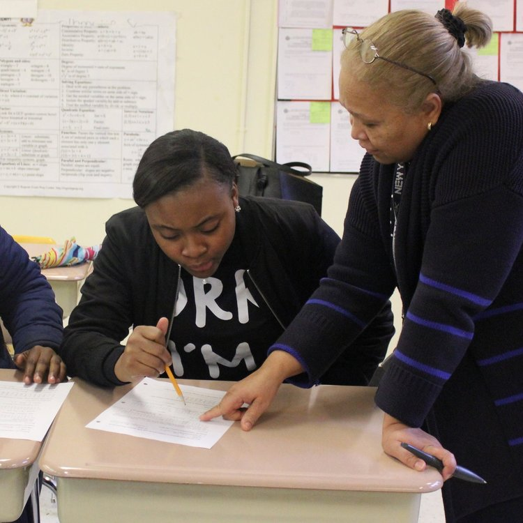 Teacher assisting a student.