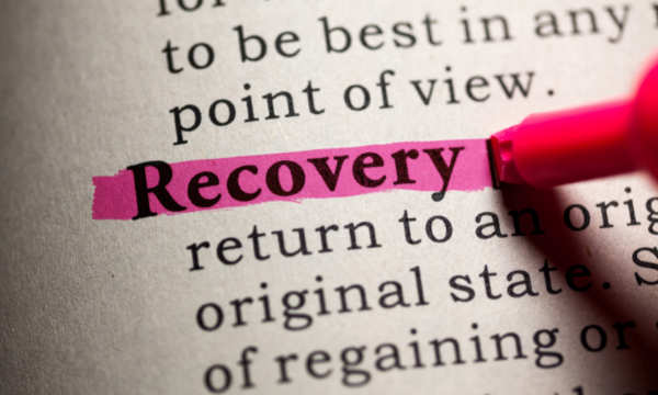 The words 'recovery' highlighted in pink in a book.