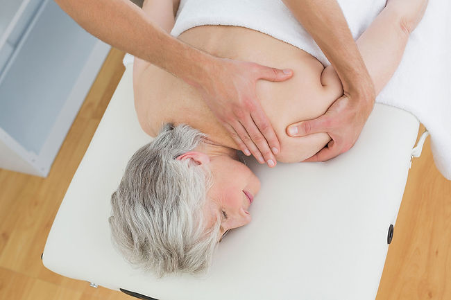 physiotherapist-massaging-senior-womans-