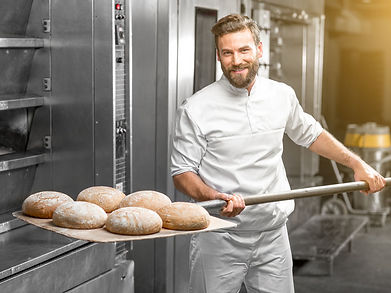Chef holding baked bread rolls