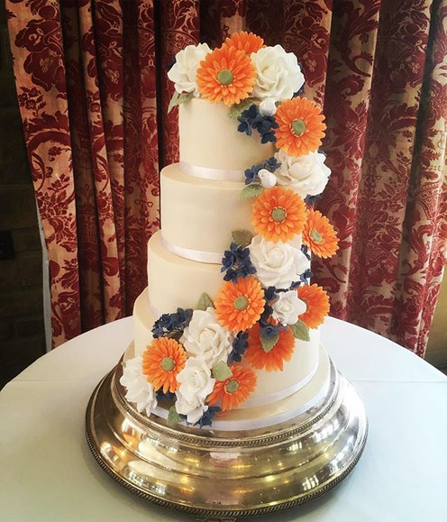 four tier wedding cake, orange wedding cake, orange and blue wedding cake, south lodge wedding cake, floral wedding cake, flower cascade wedding cade, bold colour wedding cake, sigar flowers wedding cake, flowery wedding cake, Sussex wedding cake, gerbera wedding cake, rose wedding cake