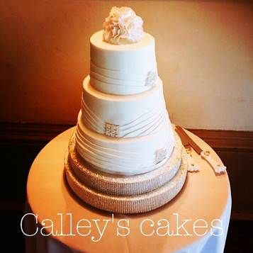 Pleated wedding cake with sugar flowers and diamontre brooch